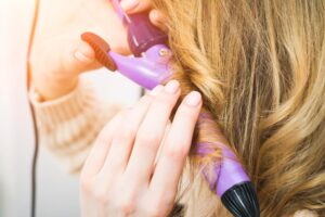 Woman curling her hair with a Curling Iron