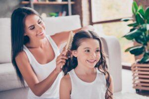 Mother brushing her daughter's hair
