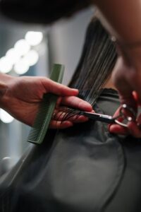 person holding hair and preparing to trim the hair at the ends